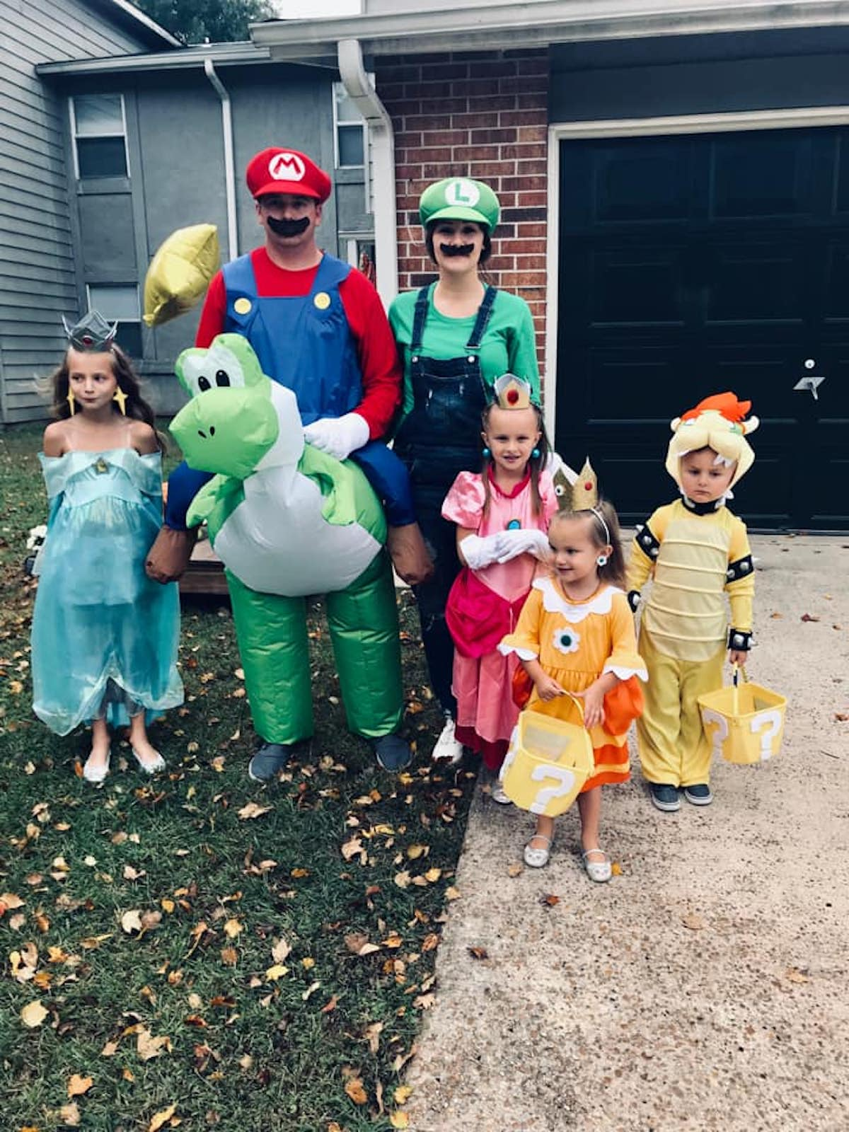 Family wearing Super Mario costumes smile in front yard.