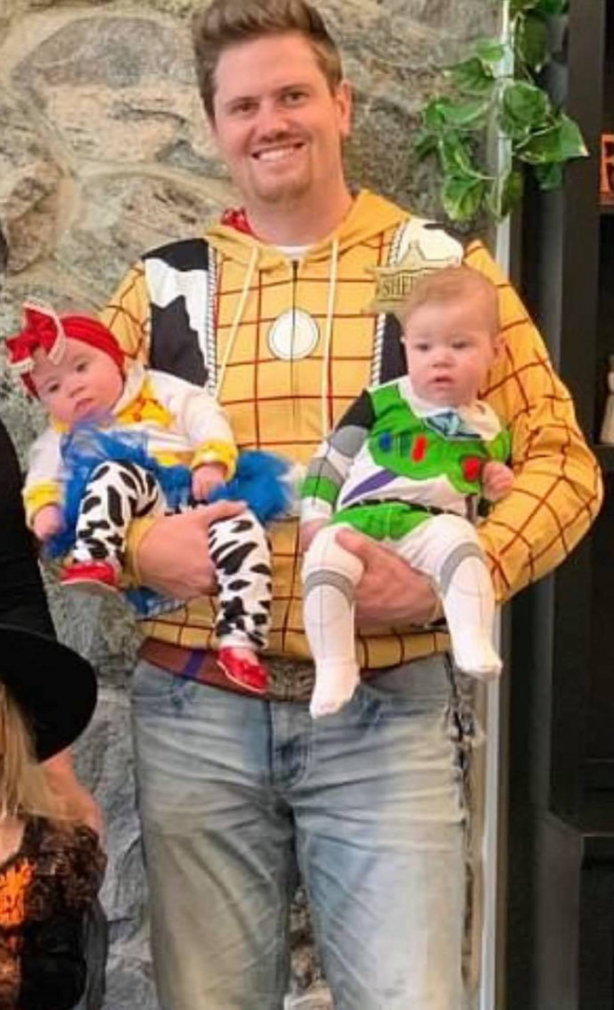 Man dressed as Woody holds babies dressed as Jessie and Buzz Lightyear.