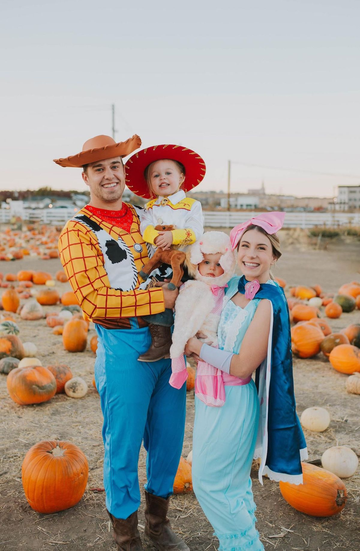 Family wearing Toy Story character costumes smile in pumpkin patch for picture.