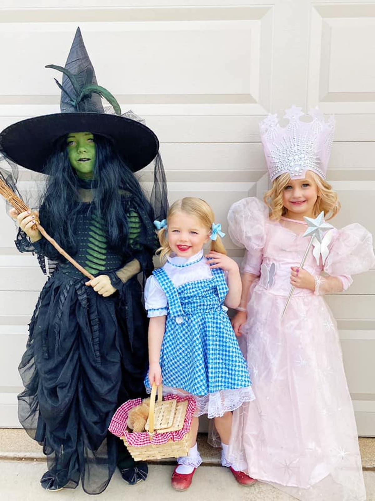 Three girls wearing Wizard of Oz character costumes smile in front of garage door.