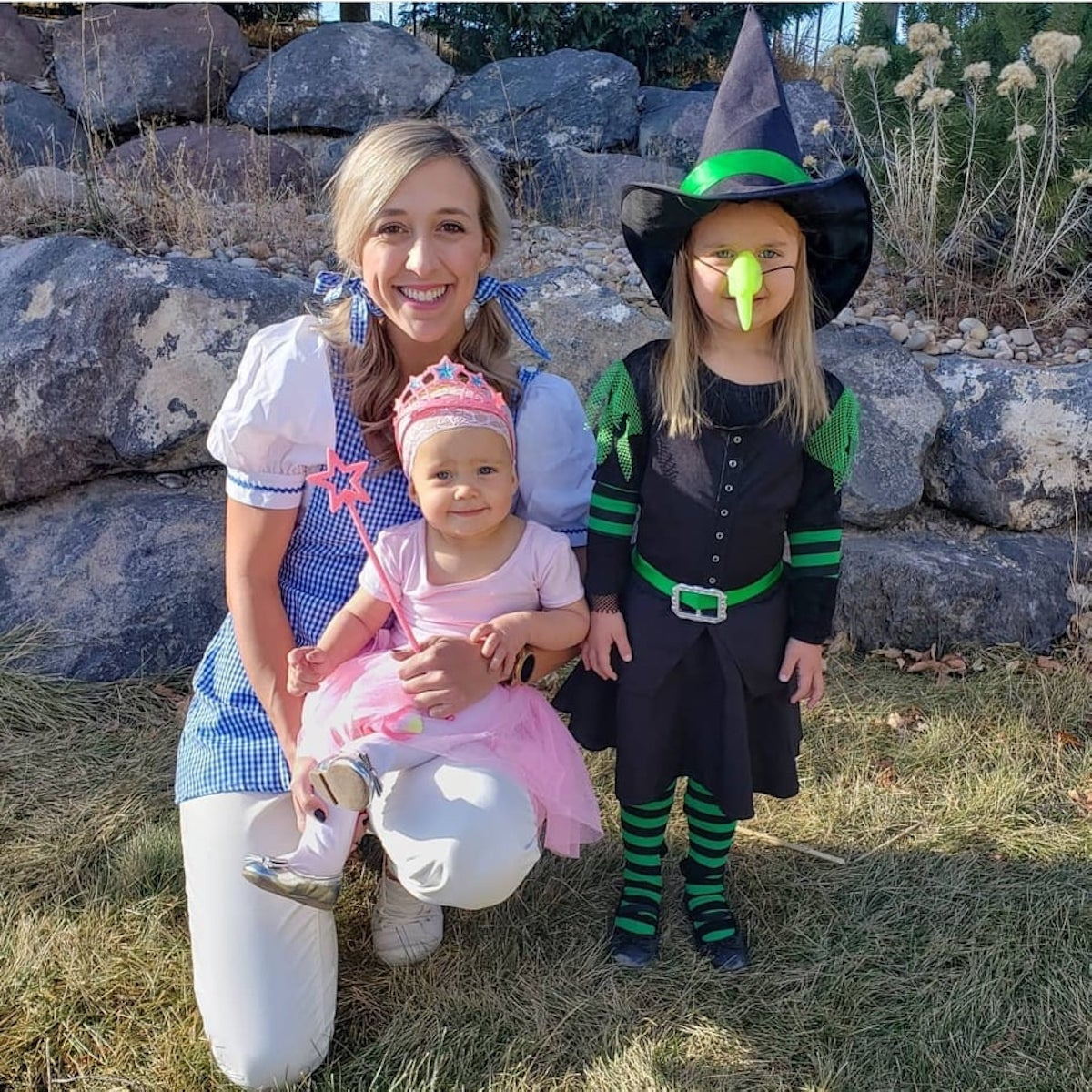 Woman and two girls wearing Wizard of Oz costumes smile in front of rock wall.