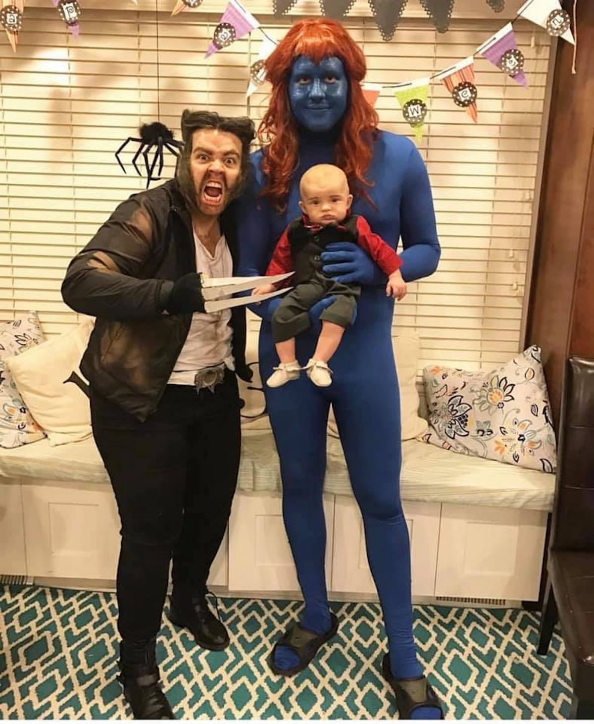 Family wearing X-Men character costumes smile in front of Halloween decorations.