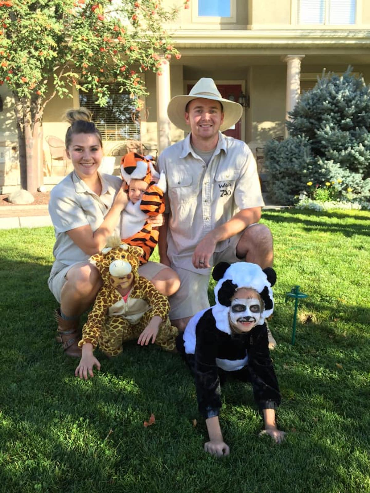 Family wearing zoo keeper and animal costumes smiles on front lawn.