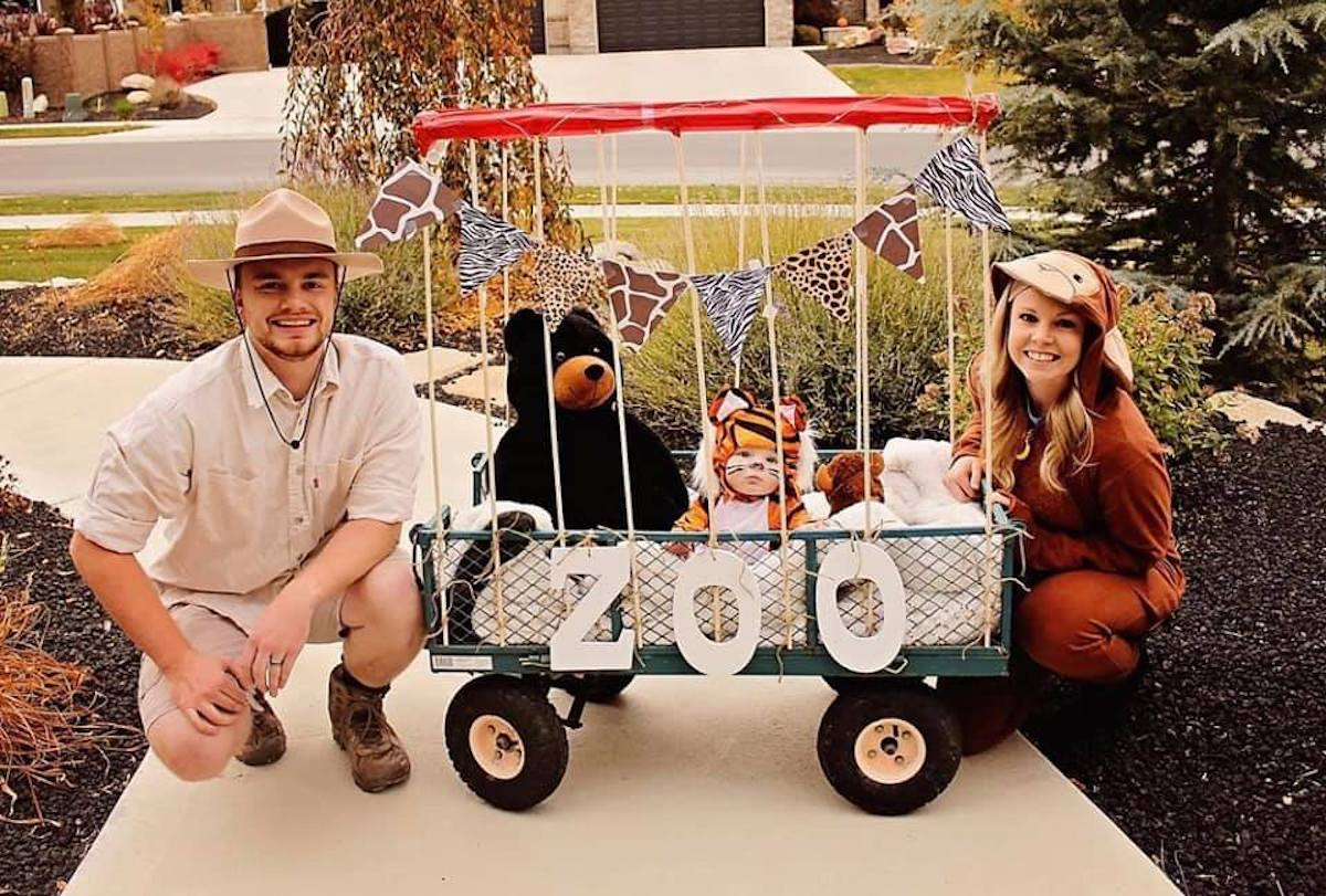 Man wearing zoo keeper costume and woman and baby wearing animal costumes smile next to DIY cage.