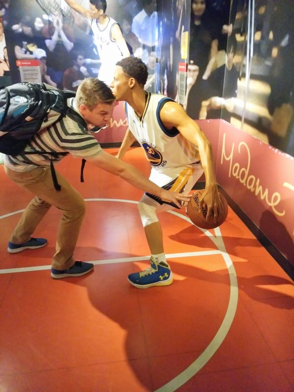 Man pretending to play basketball with wax figure from Madame Tussauds San Francisco.