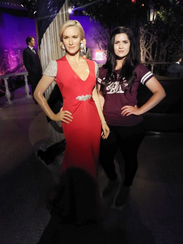 Woman standing next to wax figure in Tussauds San Francisco.