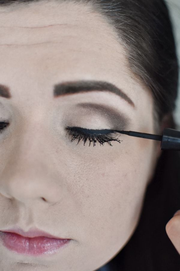 Woman applying eye liner during an easy smokey eye tutorial