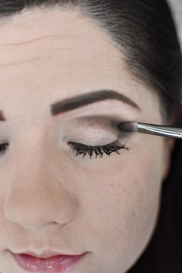 Woman applying dark eye shadow during an easy smokey eye tutorial