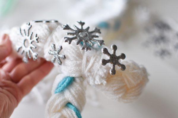 Adding snowflake stickers to a DIY Elsa yarn braid