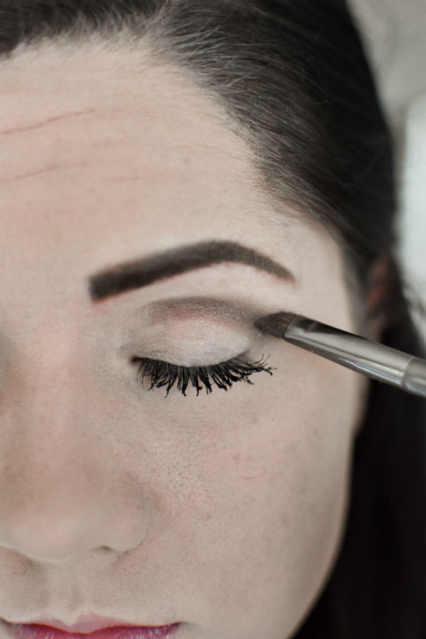 Woman applying crease eye shadow during an easy smokey eye tutorial