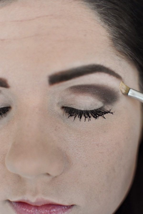 Woman applying light eye shadow during an easy smokey eye tutorial
