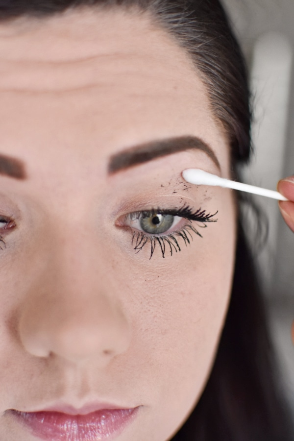 Woman cleaning mascara mistakes during an easy smokey eye tutorial