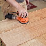 Sanding down a kitchen table. Check out my beginner's guide to refinishing a table for more tips!