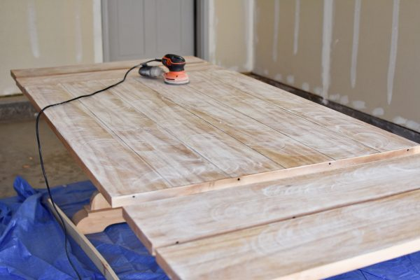 Sanding down a kitchen table in between coats of finish.