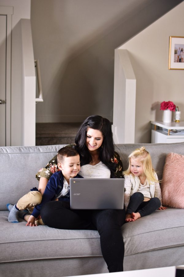 Mom sits with two kids while working from home