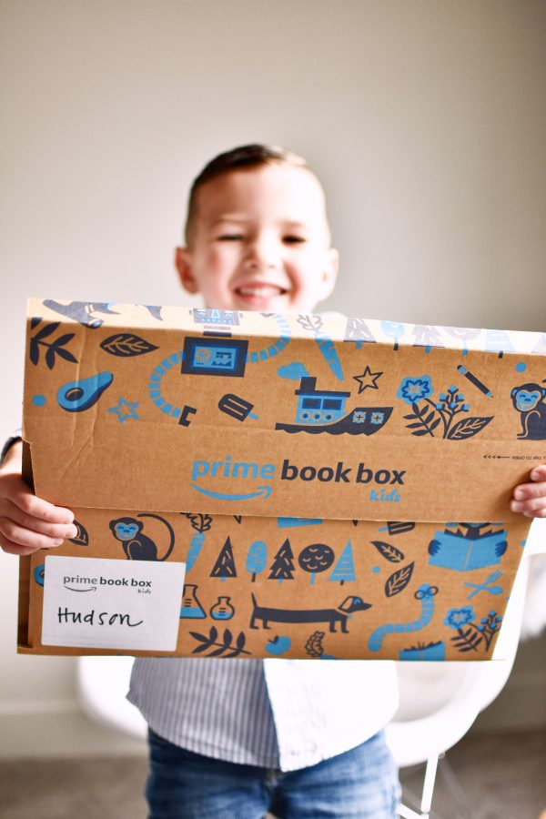 Little boy holds up Prime Book Box