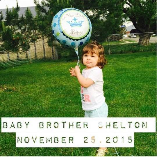 Baby girl holds a blue balloon to announce a new baby brother.