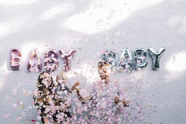 Family surrounded by pink confetti to announce baby's gender.