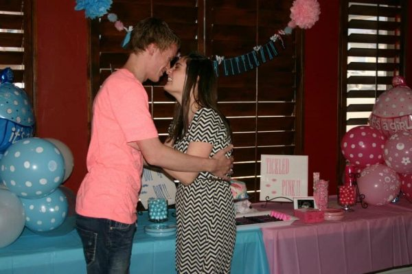 Couple embraces at their gender reveal party.