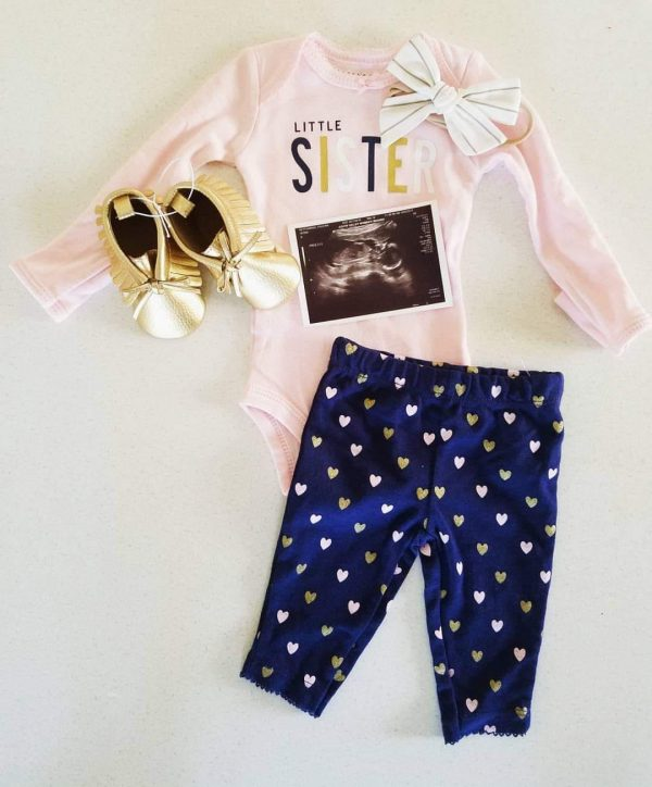 Flat lay of an ultrasound picture and baby outfit.