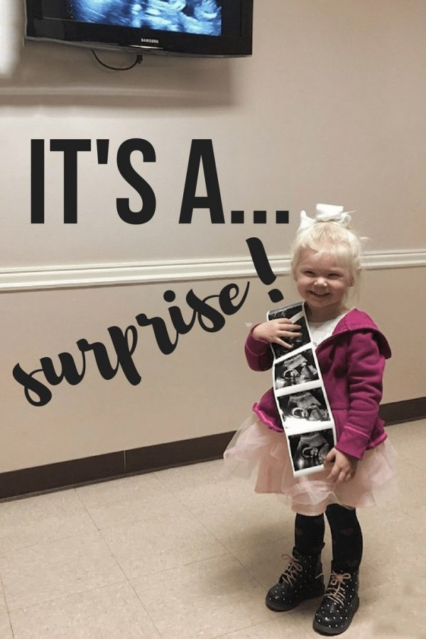 Little girl holds up ultrasound photo.