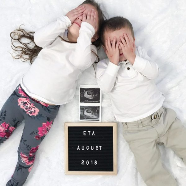Two siblings with an ultrasound baby announcement