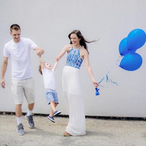 Family holds blue balloons for a gender reveal.