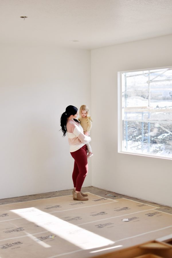 Mom holds daughter and thinks about the steps to building a home