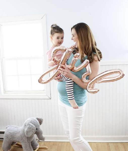 Mom holds girl balloon and daughter on her baby bump.