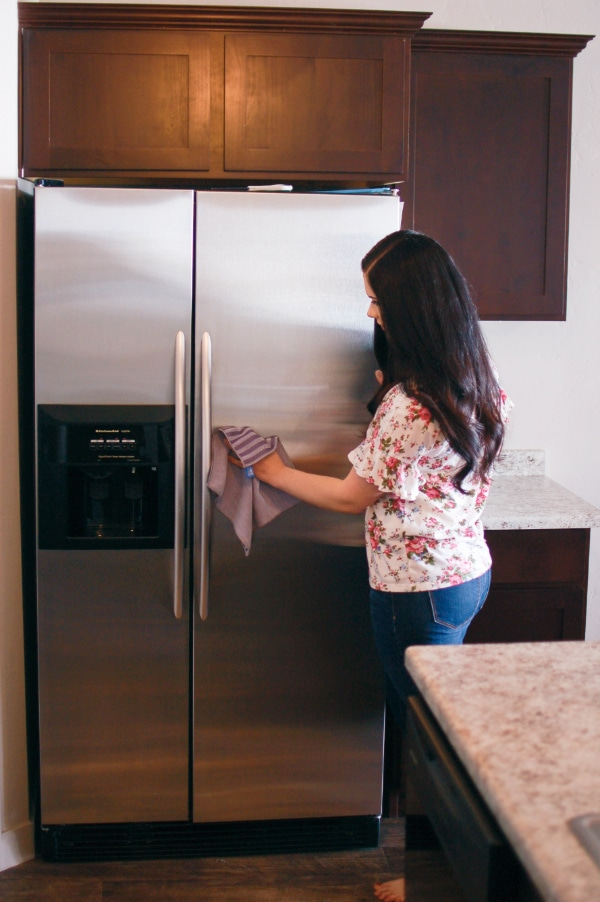 Woman wipes down her fridge during spring cleaning.