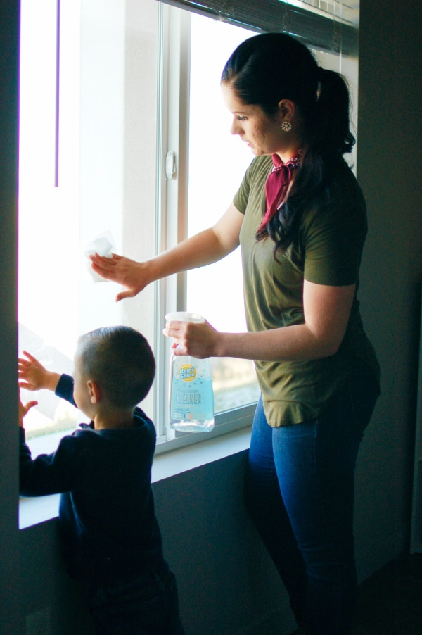 Mom and son clean windows during spring cleaning.