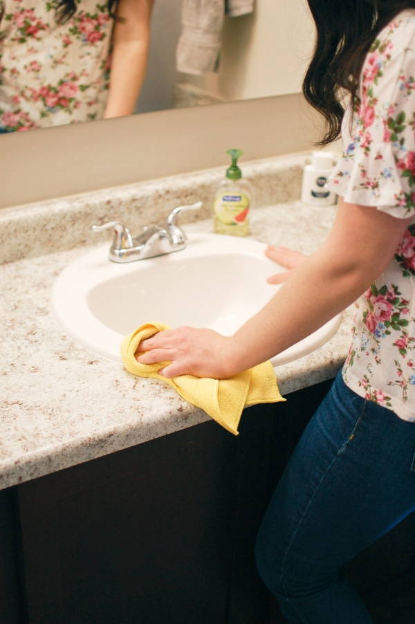 Woman cleans bathroom vanity with microfiber cleaning cloth.