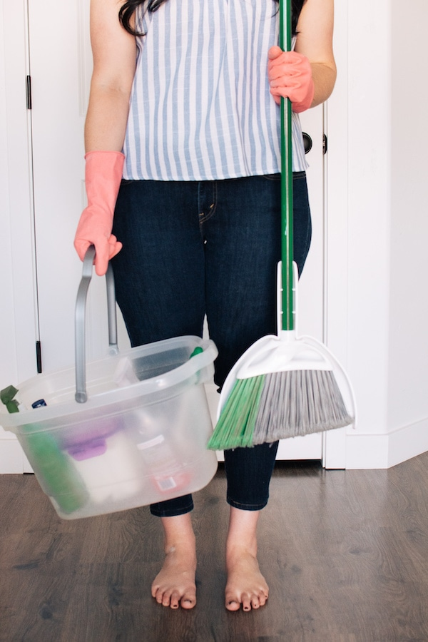 Woman holds broom and cleaning bucket.