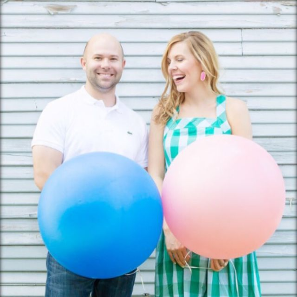 Husband and wife hold blue and pink balloons for a twin gender reveal.