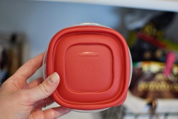 Woman holds an Easy Find Lids container, which is a great pantry organization solution.