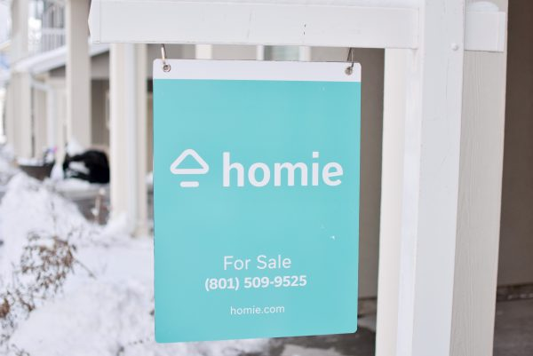 Yard sign shows a Homie real estate listing.