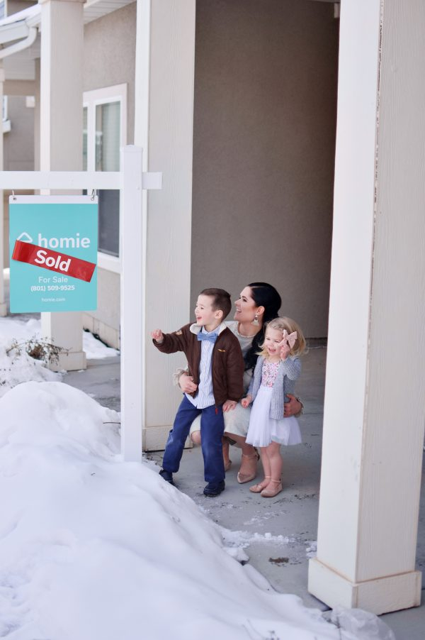 A mom and two kids stand next to their Homie sign in front of their sold house.