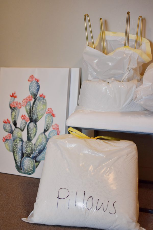 Covering soft items with plastic bags is on of the best packing and moving tips.
