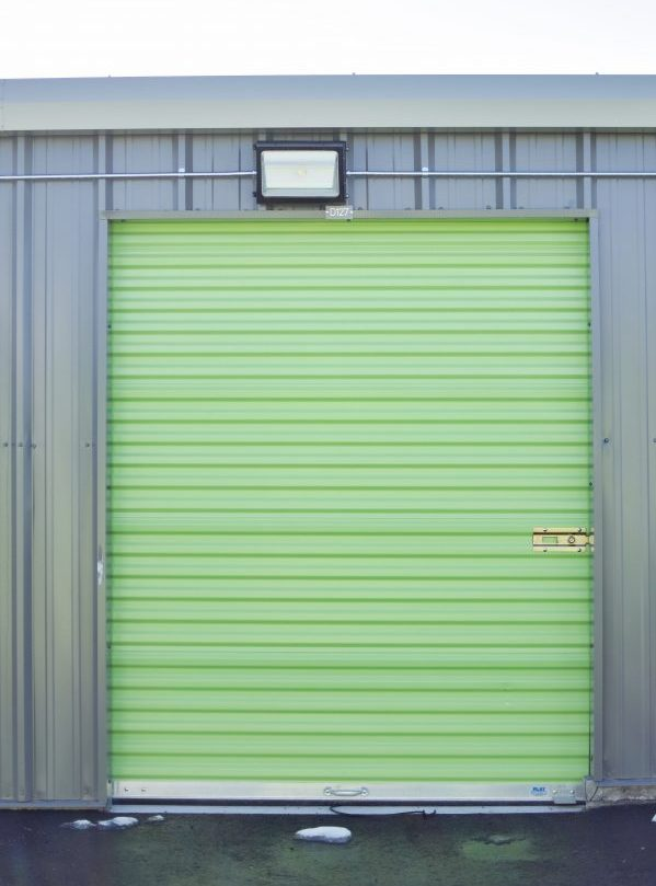A green Extra Space storage unit door