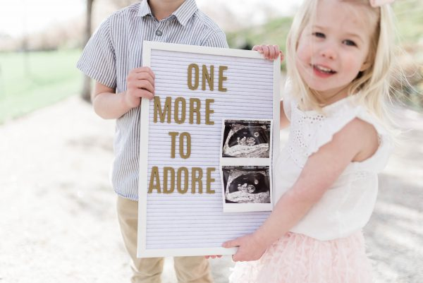 Brother and sister hold up a baby announcement letter board.
