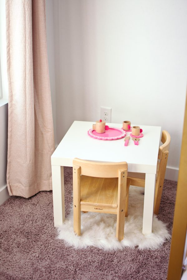 A white rug is used for decorating in this girls bedroom.