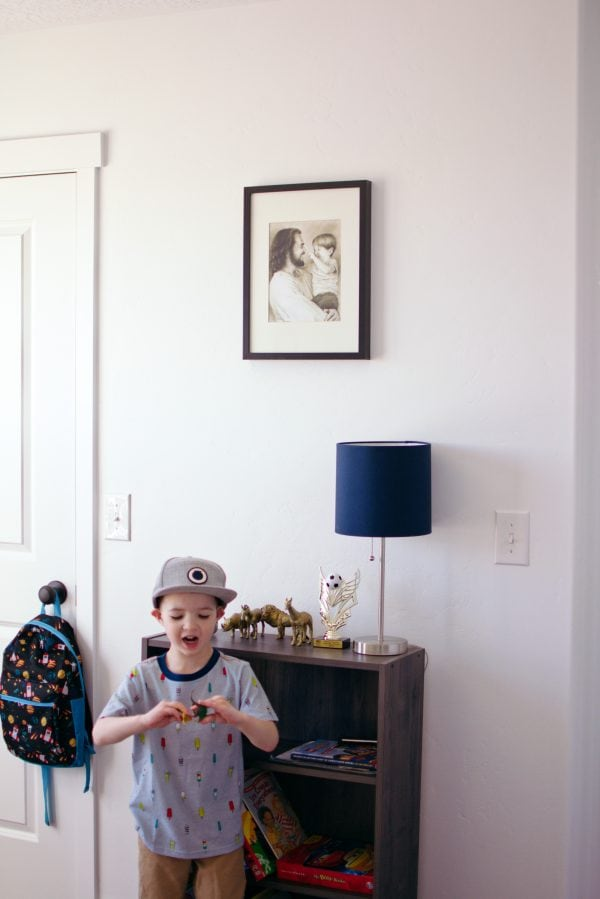 A picture hangs on the wall in this little boys bedroom.