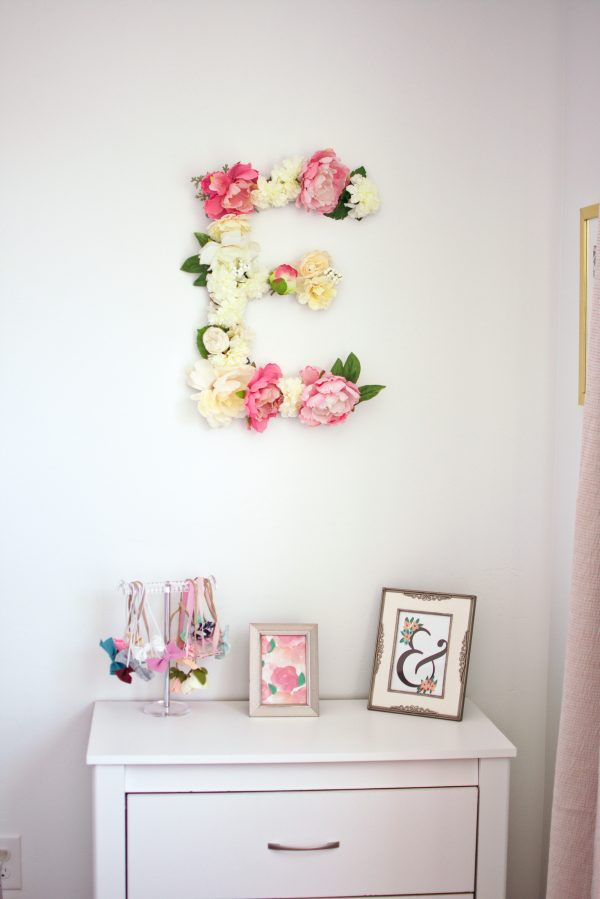 A floral letter hangs on the wall in this little girls bedrrom.