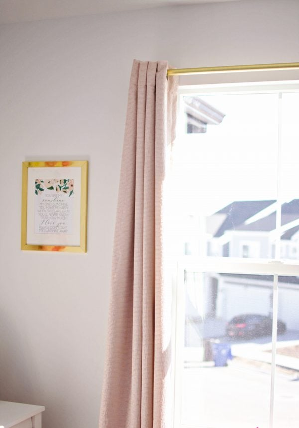 Dusty pink curtains hang in this little girls bedroom.