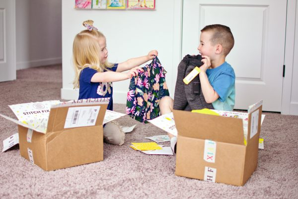 A brother and sister hold up their favorite items from their Stitch Fix for kids.