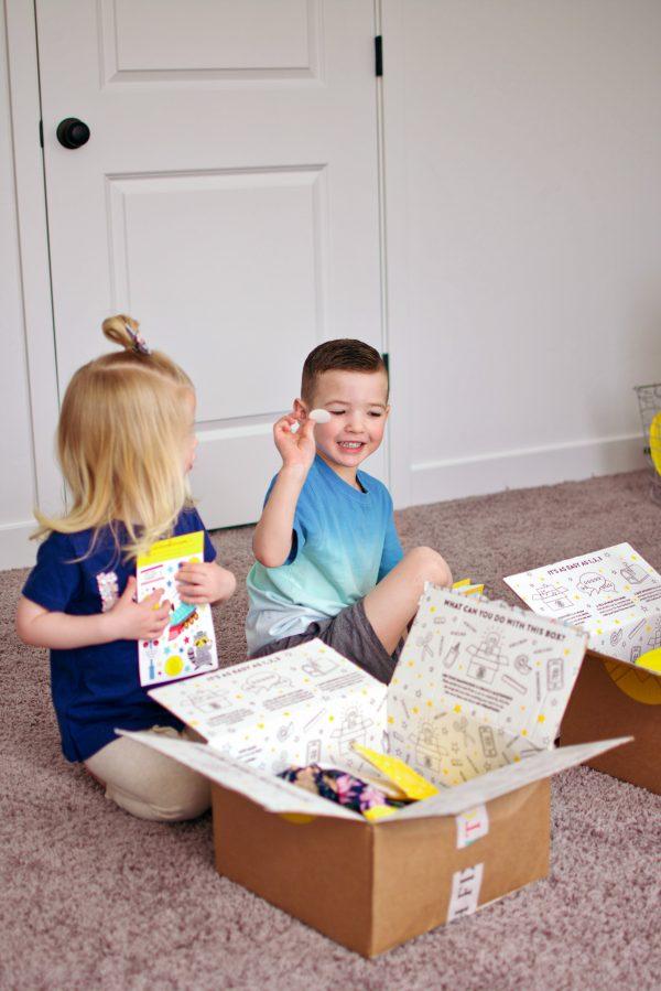 Little boy holds up a sticker from his Stitch Fix Kids box.