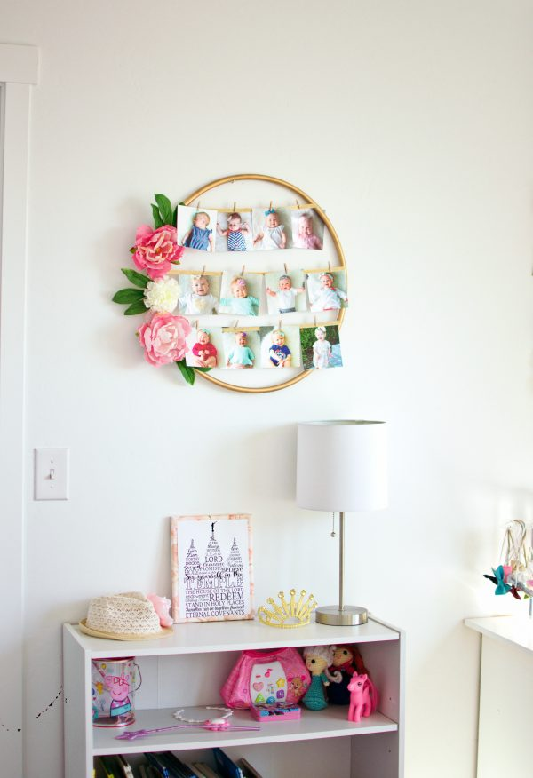 A hoop photo frame from diy home projects ideas hangs on the wall in this toddler girls bedroom.