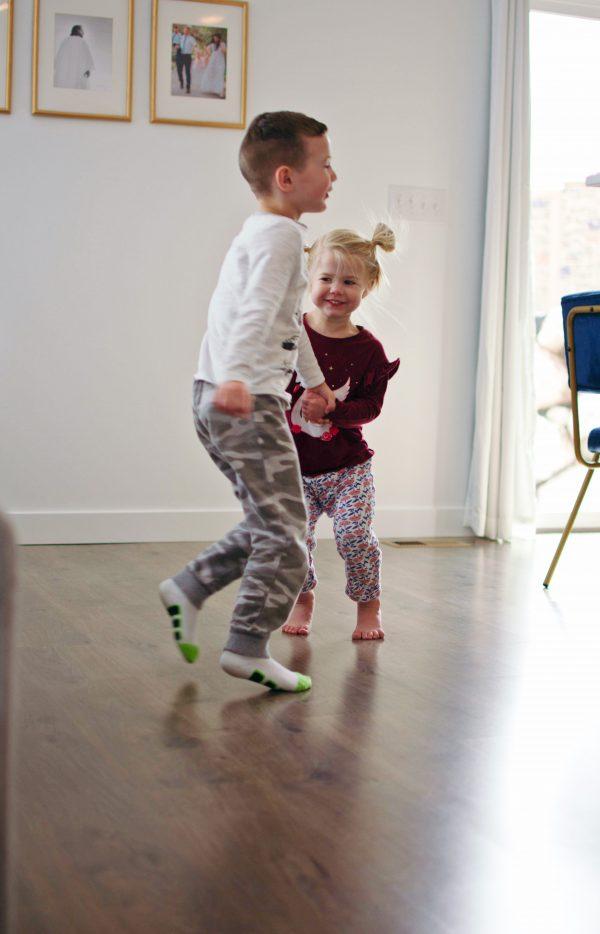 Two kids dance on their clean laminate floor.