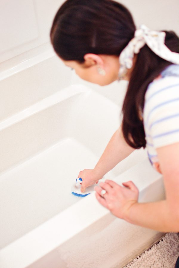 Mom scrubs a tub and follows her cleaning tips for the bathroom.