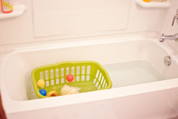 A laundry basket in the bathtub with toys inside.